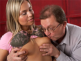 A young, blonde girl and a middle aged man are in a room together. He undresses her, first taking her bra off and playing with her tits. Then he takes